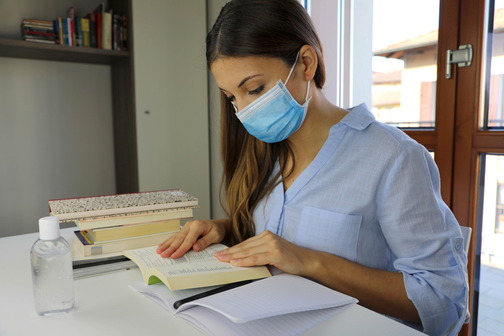 COVID-19 Pandemic Coronavirus Home Schooling Student Girl with Surgical Mask Studying from Home. Distance learning quarantine young woman reading and studying from home for virus disease 2019-nCoV.